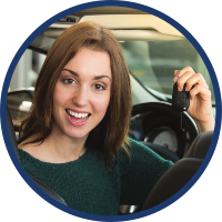 Smiling woman holding key in her new car